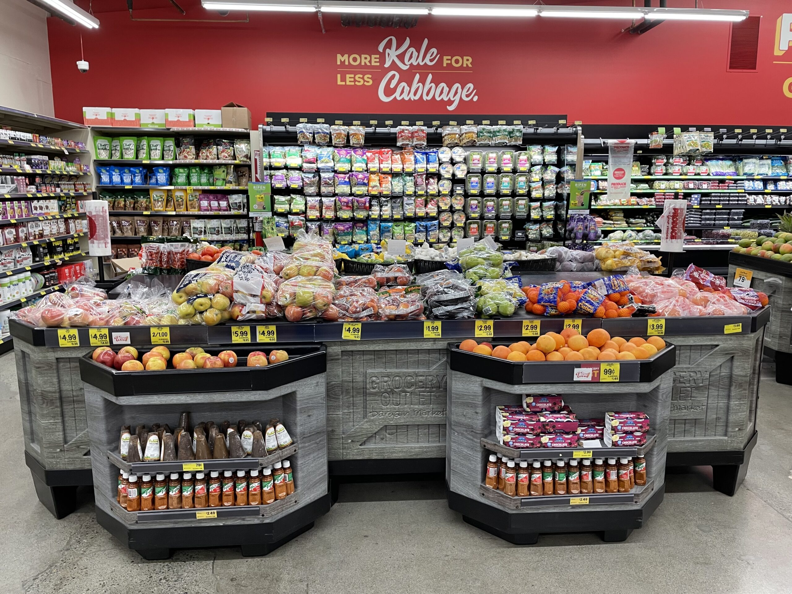 Grocery Outlet Bargain Markets In-Store Orchard Bins With Apples And Oranges Sitting On Top Of Display Bin Shelving With Salad Racks Hanging In The Background